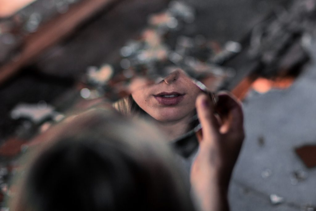 a woman holds up a mirror fragment to look at her reflection
